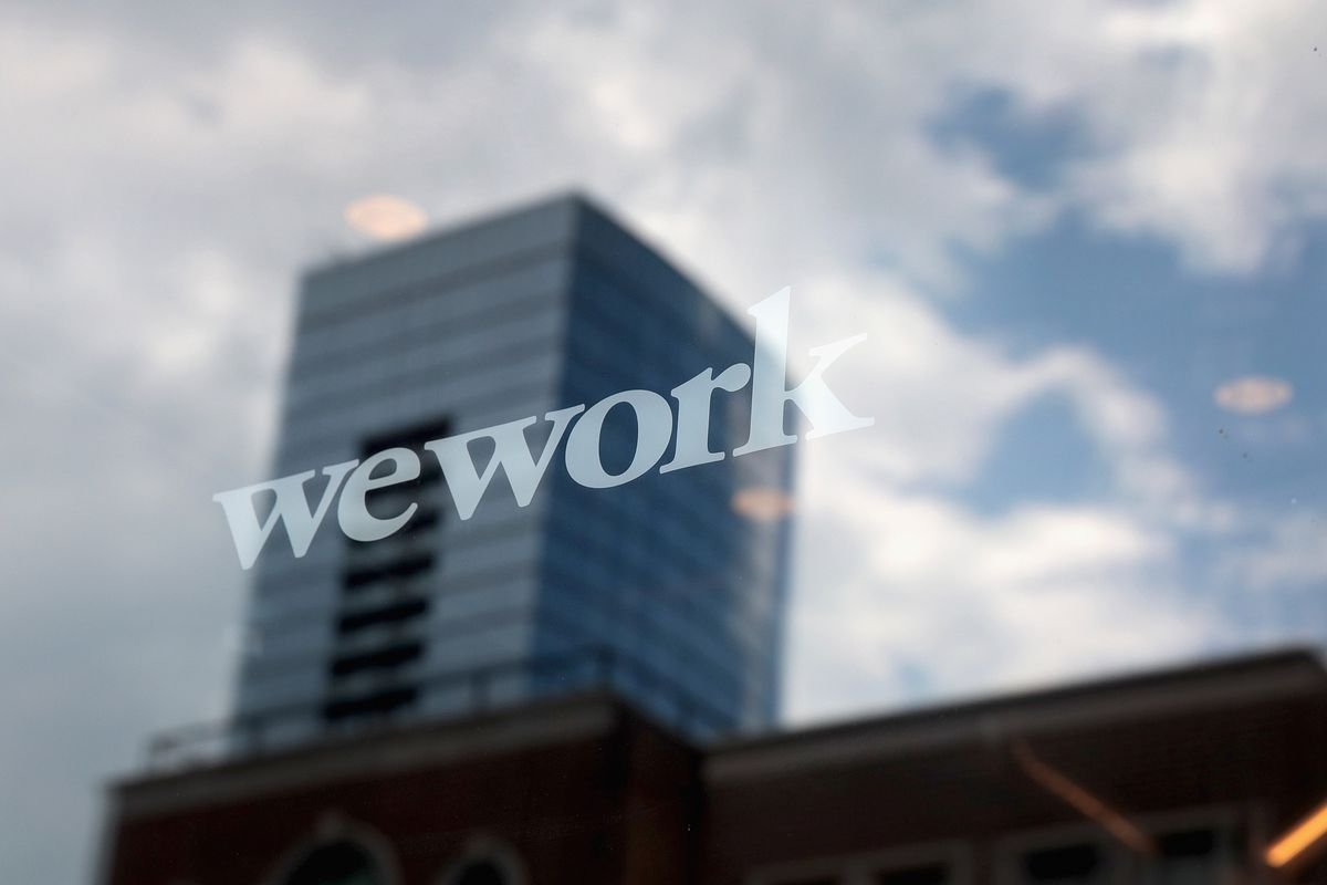 A WeWork logo printed on a glass building, with the sky reflected behind it.