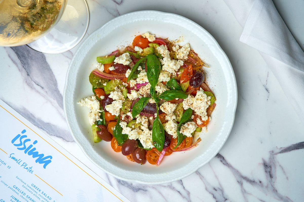 An overhead shot of a plate of tomatoes and feta with a menu sitting in one corner of the marble table.