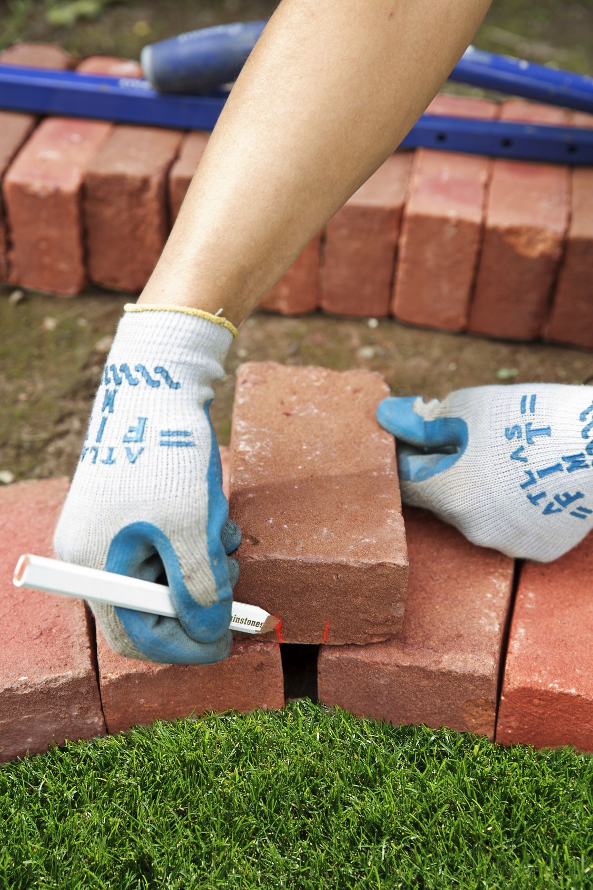 Man Marks Bricks To Fill Gaps In Curves For Brick Garden Edging