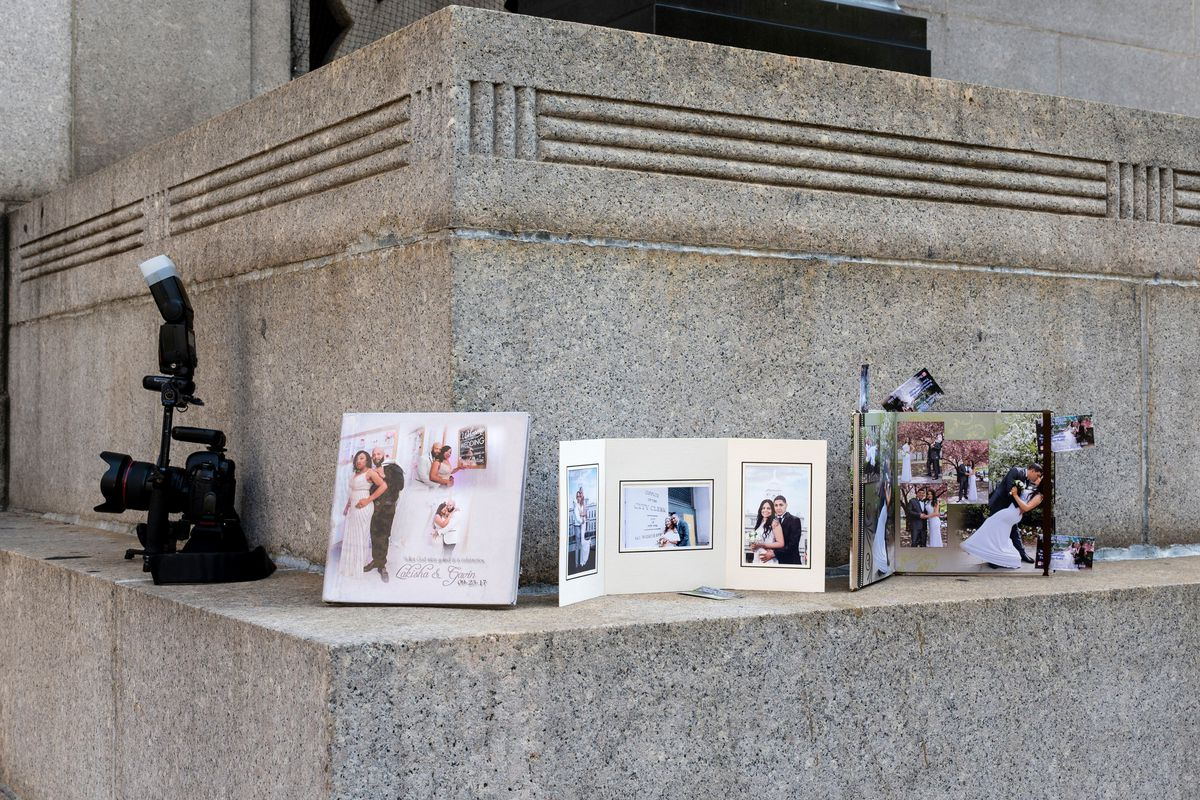 A photographer displays their portfolio on the steps of the Marriage Bureau in Lower Manhattan on the first day of its reopening since COVID, July 23, 2021.