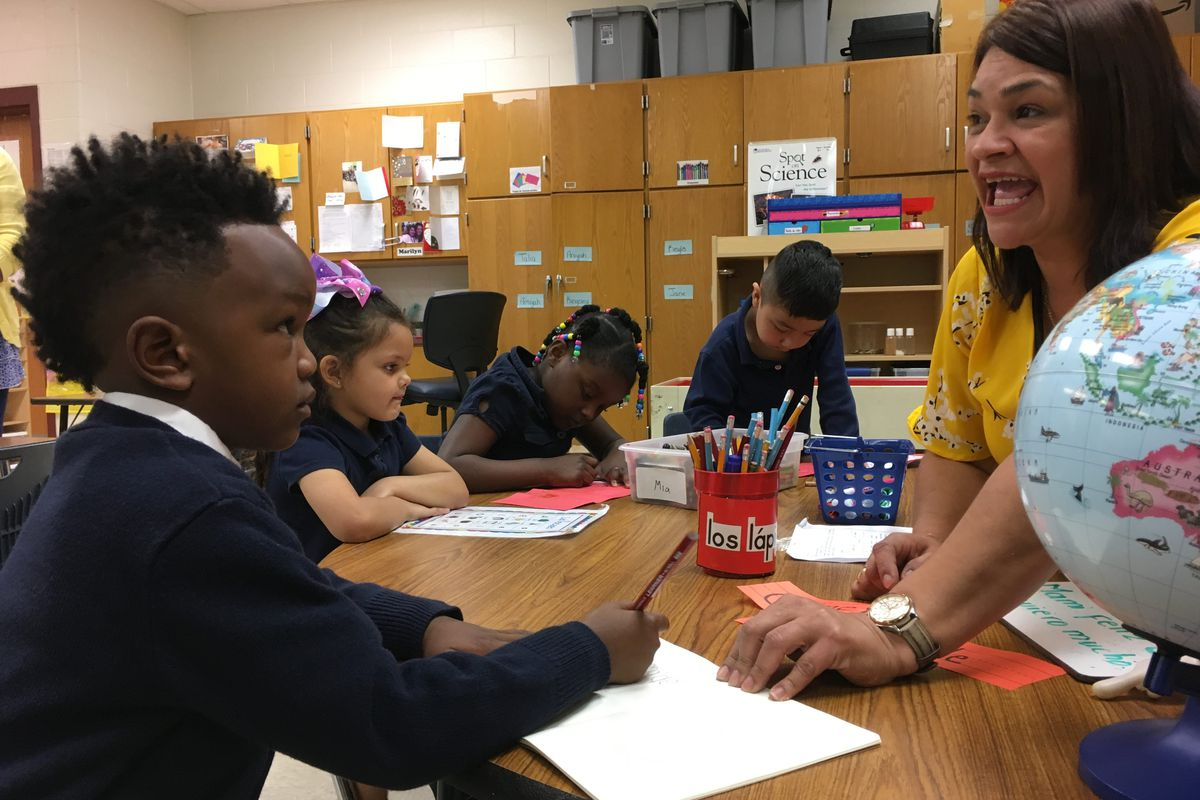 Pre-K teacher Maria Rodriguez sounds out words in Spanish to help 5-year-old Joshua Robinson with a writing exercise. Global Preparatory Academy in Indianapolis has a new bilingual prekindergarten classroom.