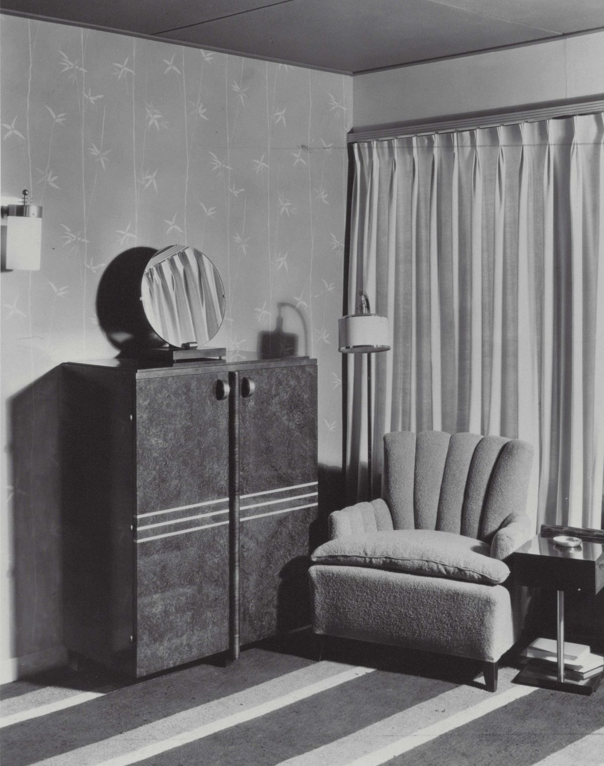 A vintage photograph of the bedroom in the Herman Miller Design for Living House. There is an armchair, dresser, and a window with drapes.