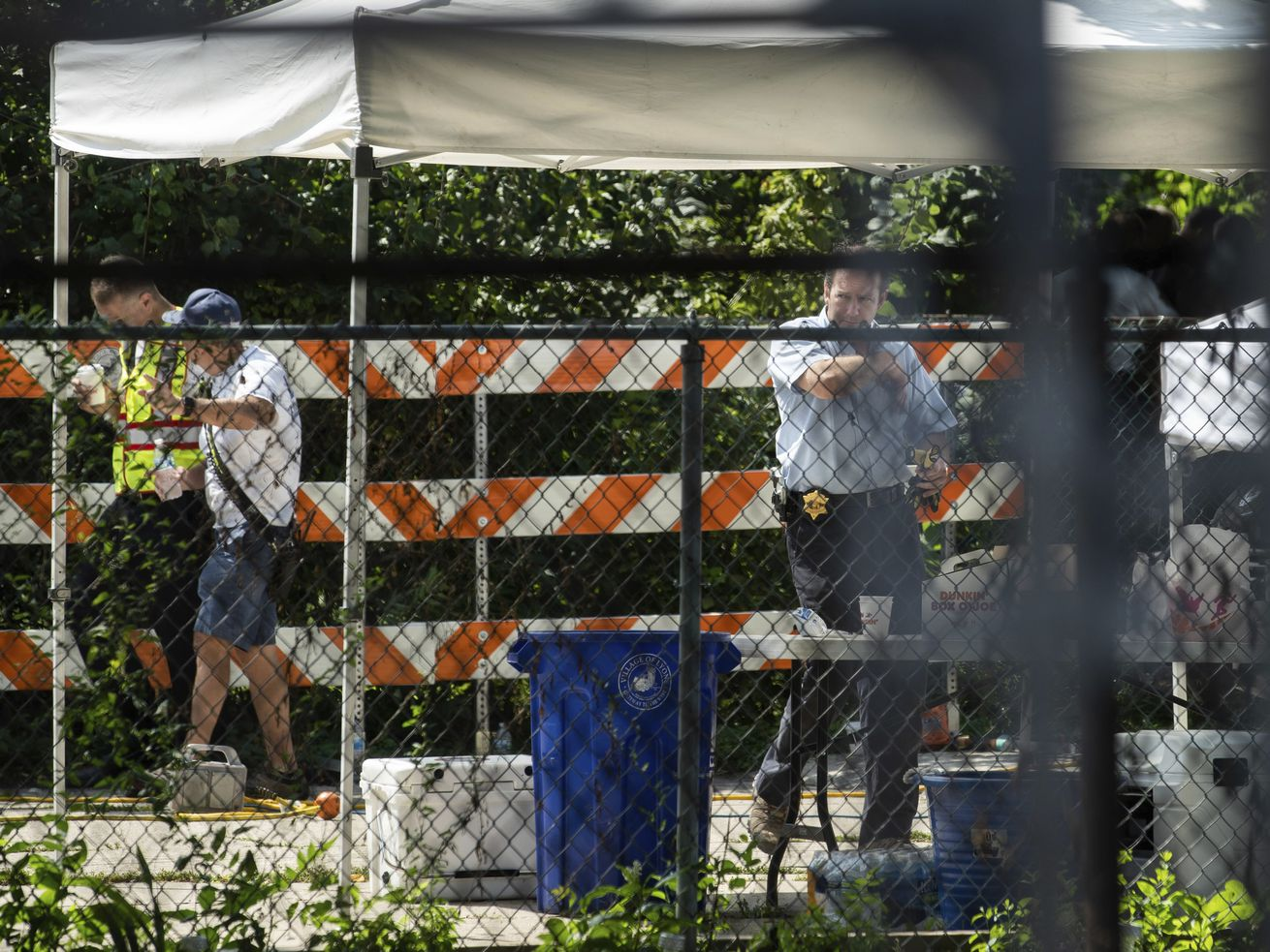 Officials walk near a house Saturday in west suburban Lyons where human remains were found in the back yard of a home where two brothers said they buried their mother and sister.