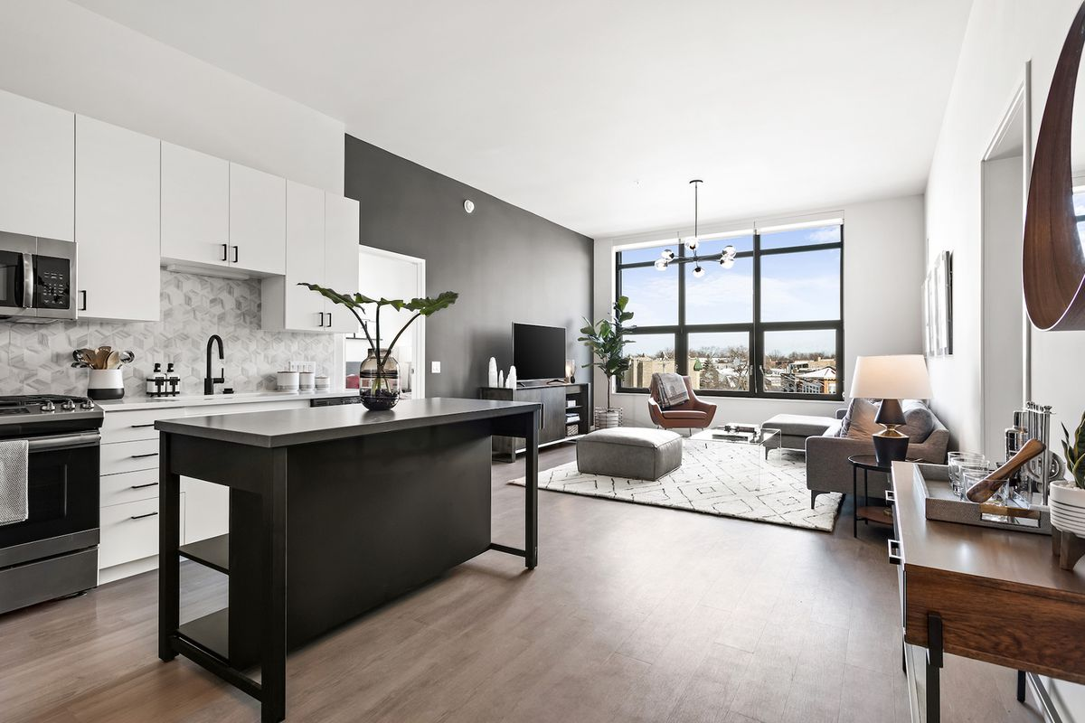 An open apartment living area with a window at the far wall and a kitchen.