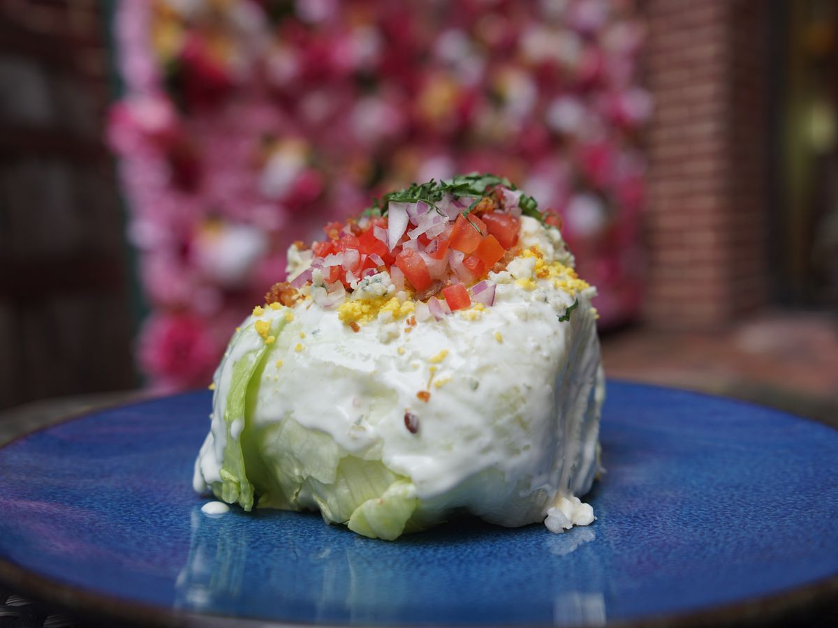 A compact wedge salad topped with baco and tomato on a blue countertop