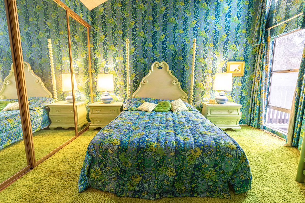 A bedroom with a solid green carpet and blue-green patterned wallpaper with matching bedding.