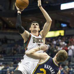 Milwaukee Bucks' Ersan Ilyasova, left, shoots over Utah Jazz Gordon Hayward during the first half of an NBA basketball game Monday, March 3, 2014, in Milwaukee. (AP Photo/Tom Lynn)