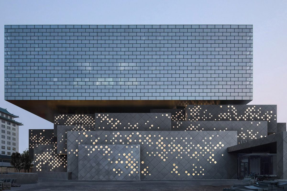 Building formed by lower portion which is series of nested stone cubes whose scale match the surrounding traditional hutong courtyard houses, while a cantilevering glass box made from windows arranged in a brick pattern comprises the upper volume