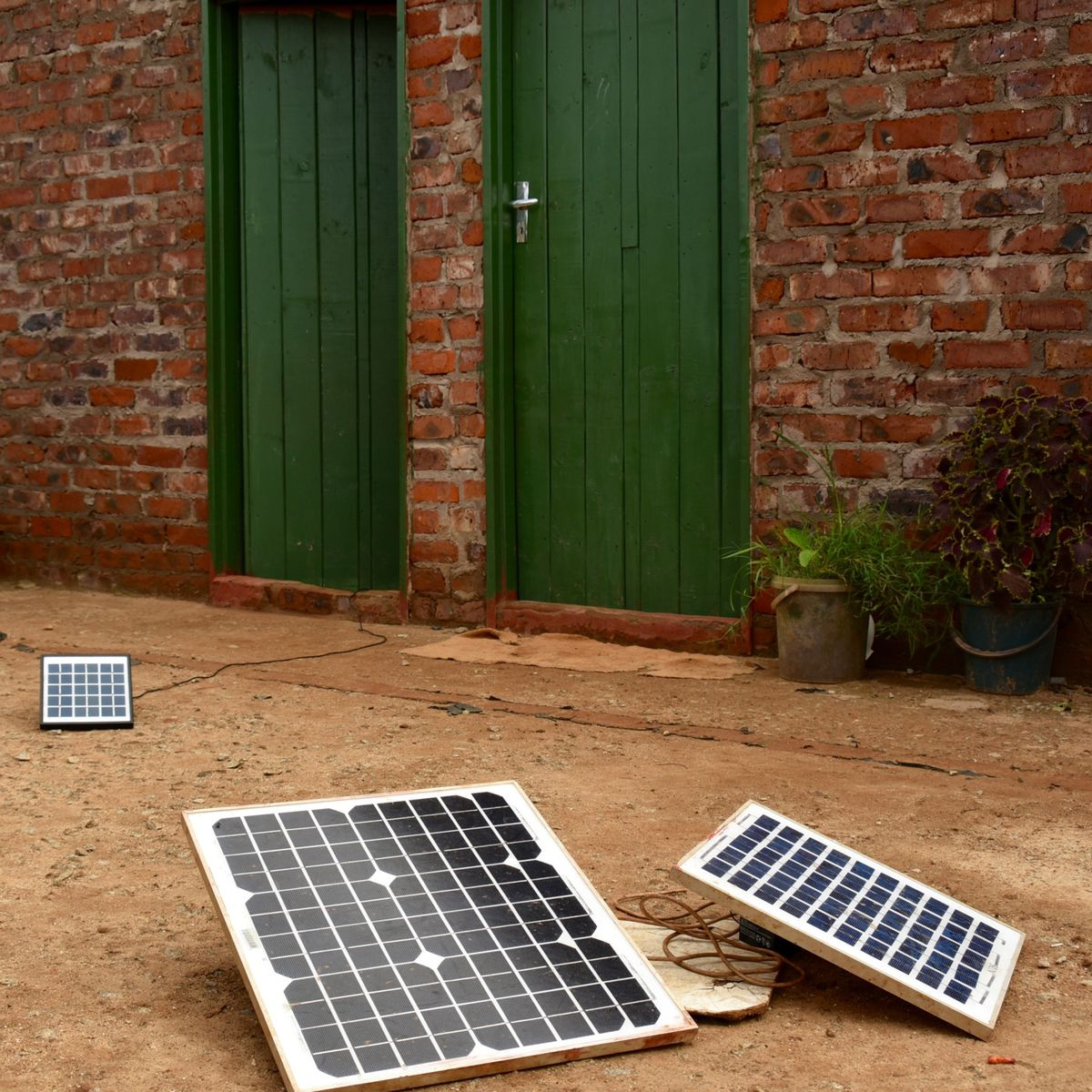 A trio of medium-sized solar panels strategically placed outside the doors of several homes sharing a courtyard