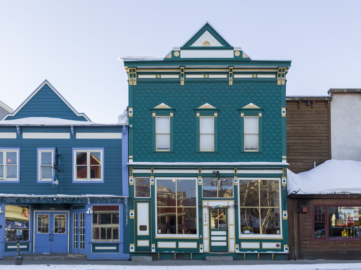 A bright blue and teal green building next to each other, in the Victorian style, in the town of Crested Butte.