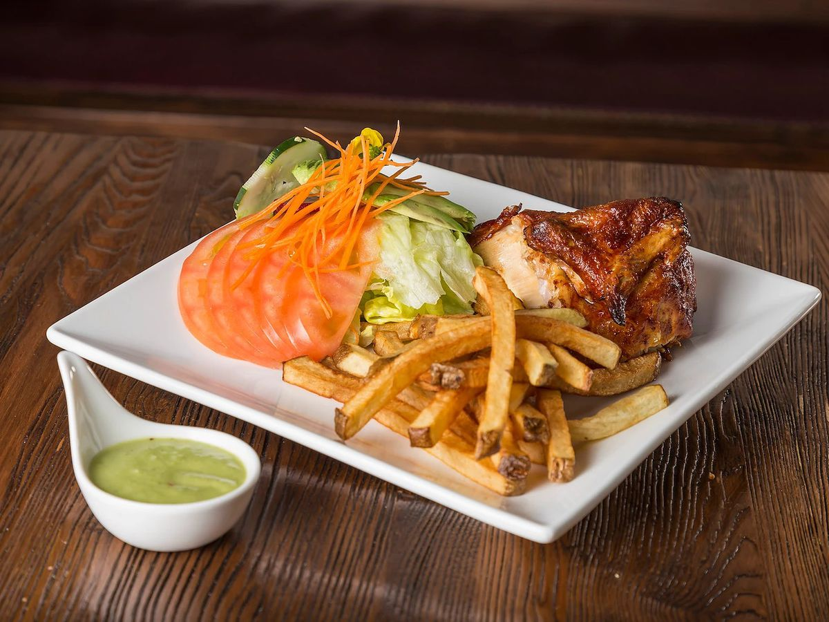 French fries, salad, and rotisserie chicken on a square white plate