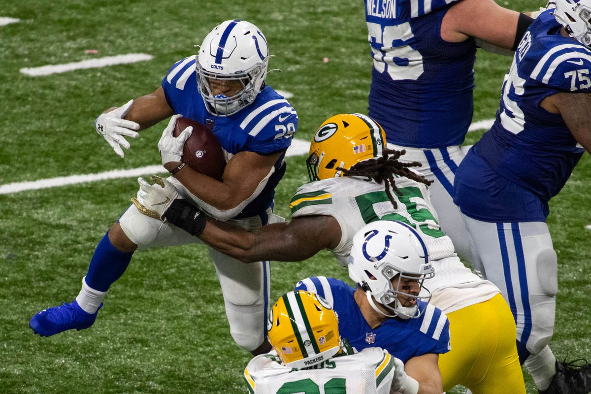Indianapolis Colts running back Jonathan Taylor (28) runs the ball against Green Bay Packers outside linebacker Za'Darius Smith (55) in overtime at Lucas Oil Stadium.