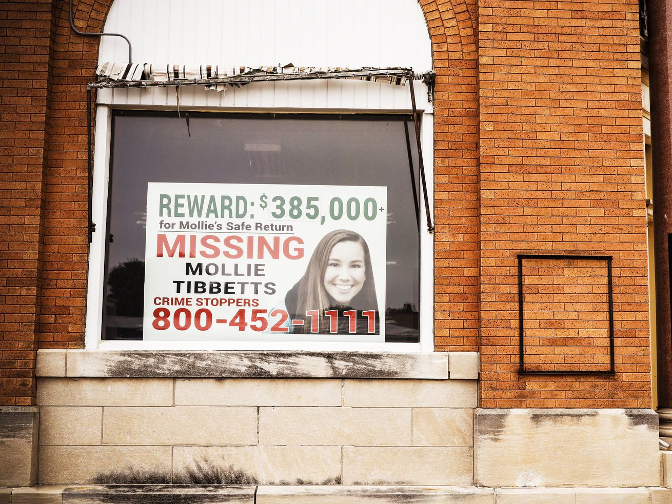 A poster for missing University of Iowa student Mollie Tibbetts hangs in the window of a local business in Brooklyn, Iowa, on August 21, 2018.
