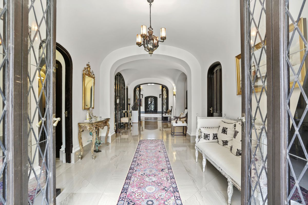A castle's long hallway has long white flooring, elegant furniture, and a chandelier.