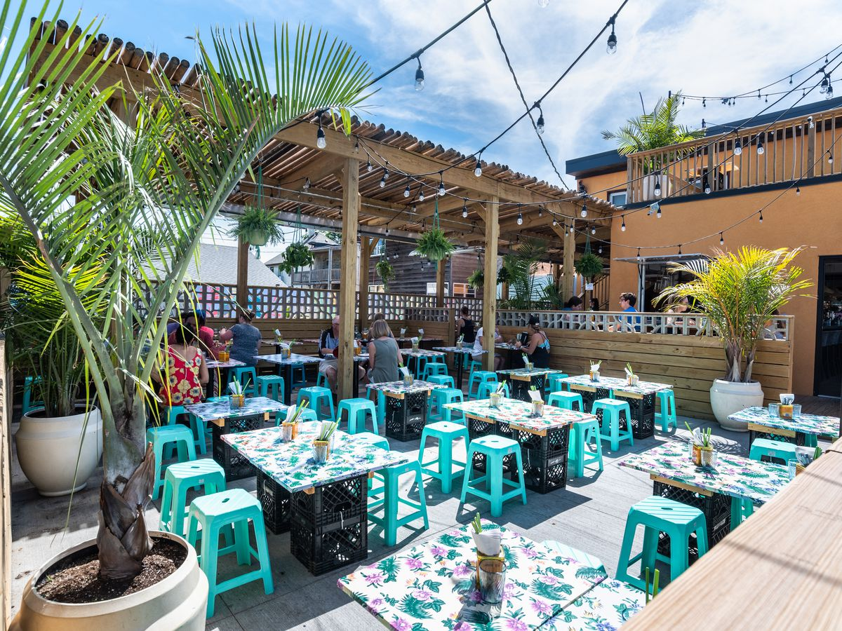 A brightly colored open-air patio with low stools and oilcloth covered tables