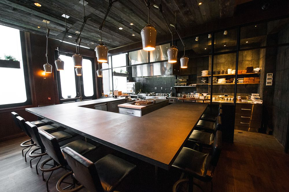 A U-shaped wooden table with dark wood furniture and hanging light fixtures.