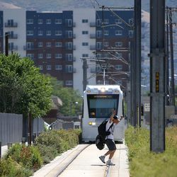 A man runs in front of the S-Line streetcar as it travels from Sugar House to South Salt Lake on Tuesday, June 27, 2017.