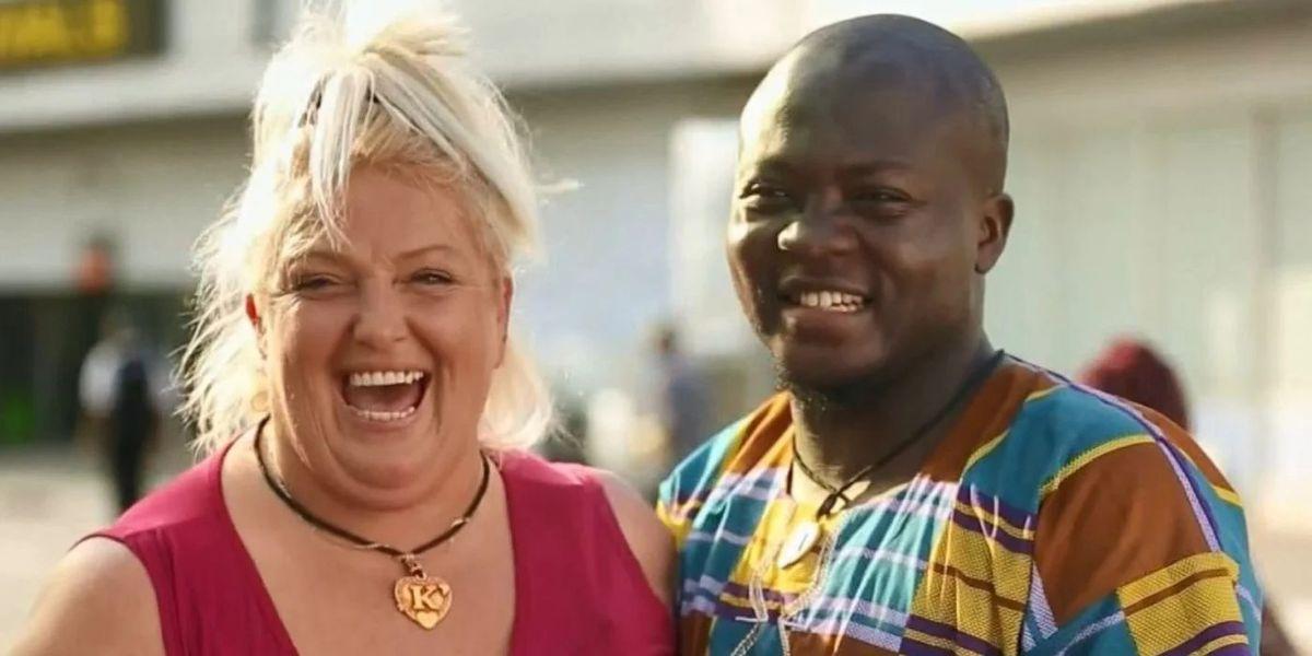 A white woman and a Black man smile.