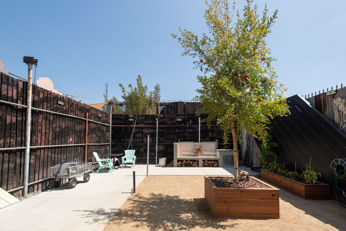 A planter box with seating and a pomegranate tree in an open lot.