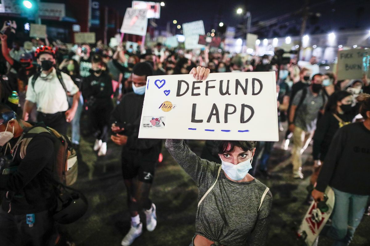 """A crowded night time protest featuring many people in masks; the camera is focused on a white woman in a grey sweatshirt who is raising a sign with blue hearts that says """"Defund LAPD."""""""