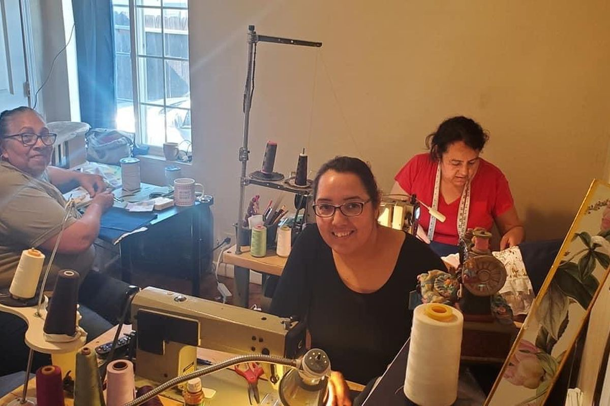 Cecilia Chairez (center) at work at her at-home seamstress shop