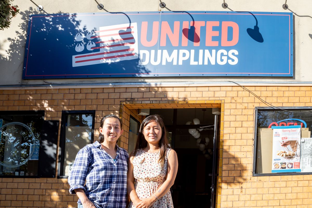 Zheng (left) and Zhu stand in front of their restaurant, United Dumplings