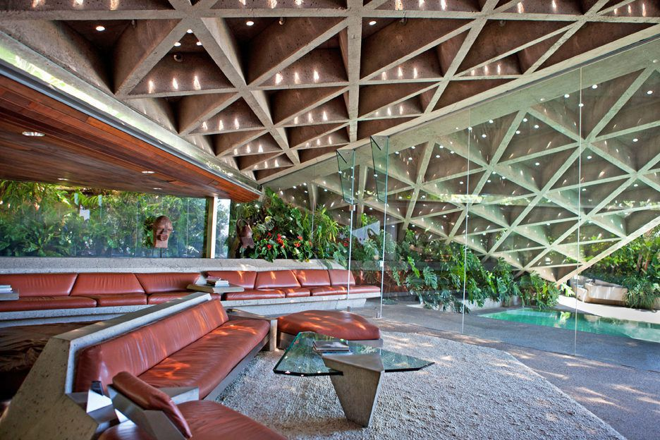 The interior of the Sheats-Goldstein house. There are red couches, a glass table, and floor to ceiling windows. The ceiling has a triangular concrete design.