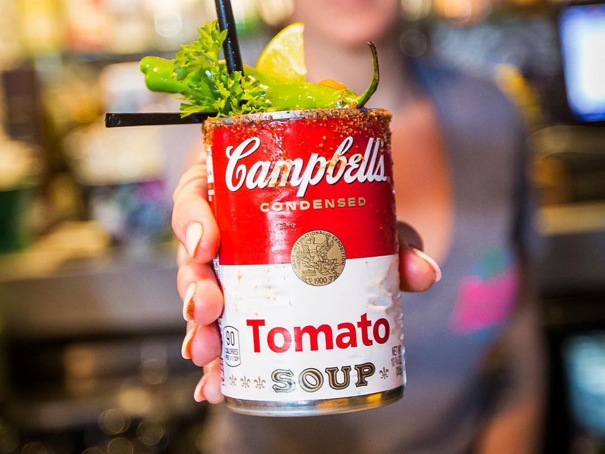 a bartender serving a bloody mary in a campbell's tomato soup can