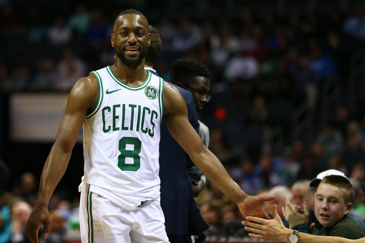 Boston Celtics guard Kemba Walker high fives players while walking down the bench during the second half against the Charlotte Hornets at Spectrum Center.