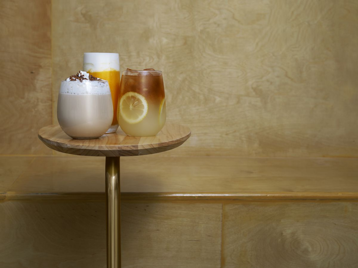 Three colorful drinks with foamy white tops and fruit sit on a small table made of light wood