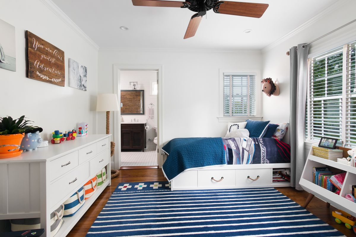 A bedroom that looks like a child, perhaps a tweener, occupies it. It has a wood floor, and there is a bed that's possibly a trundle bed in one corner. There's a long set of drawers on the opposite wall and a double row of wooden bins under a row of windows on the wall next to the bed. There are curtains as well as open slatted shades on the windows.