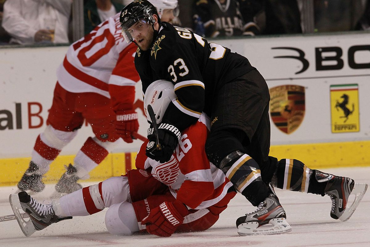 DALLAS, TX - JANUARY 03:  Alex Goligoski #33 of the Dallas Stars falls on top of Jiri Hudler #26 of the Detroit Red Wings at American Airlines Center on January 3, 2012 in Dallas, Texas.  (Photo by Ronald Martinez/Getty Images)
