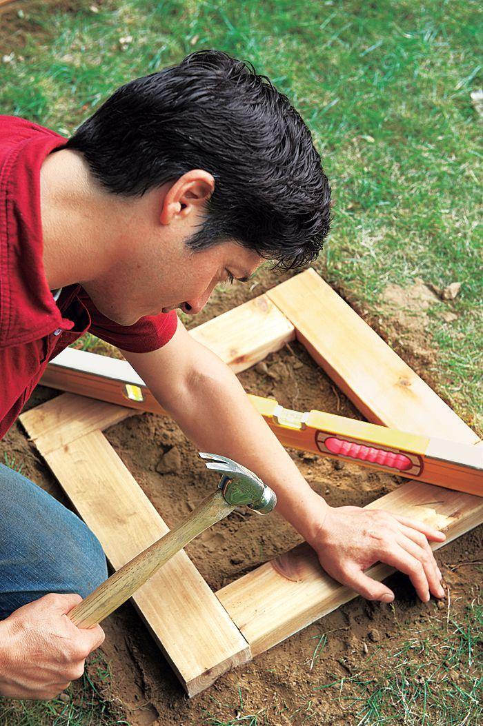 Man Nails Seat Frame Of Planter Bench Into Gravel Base