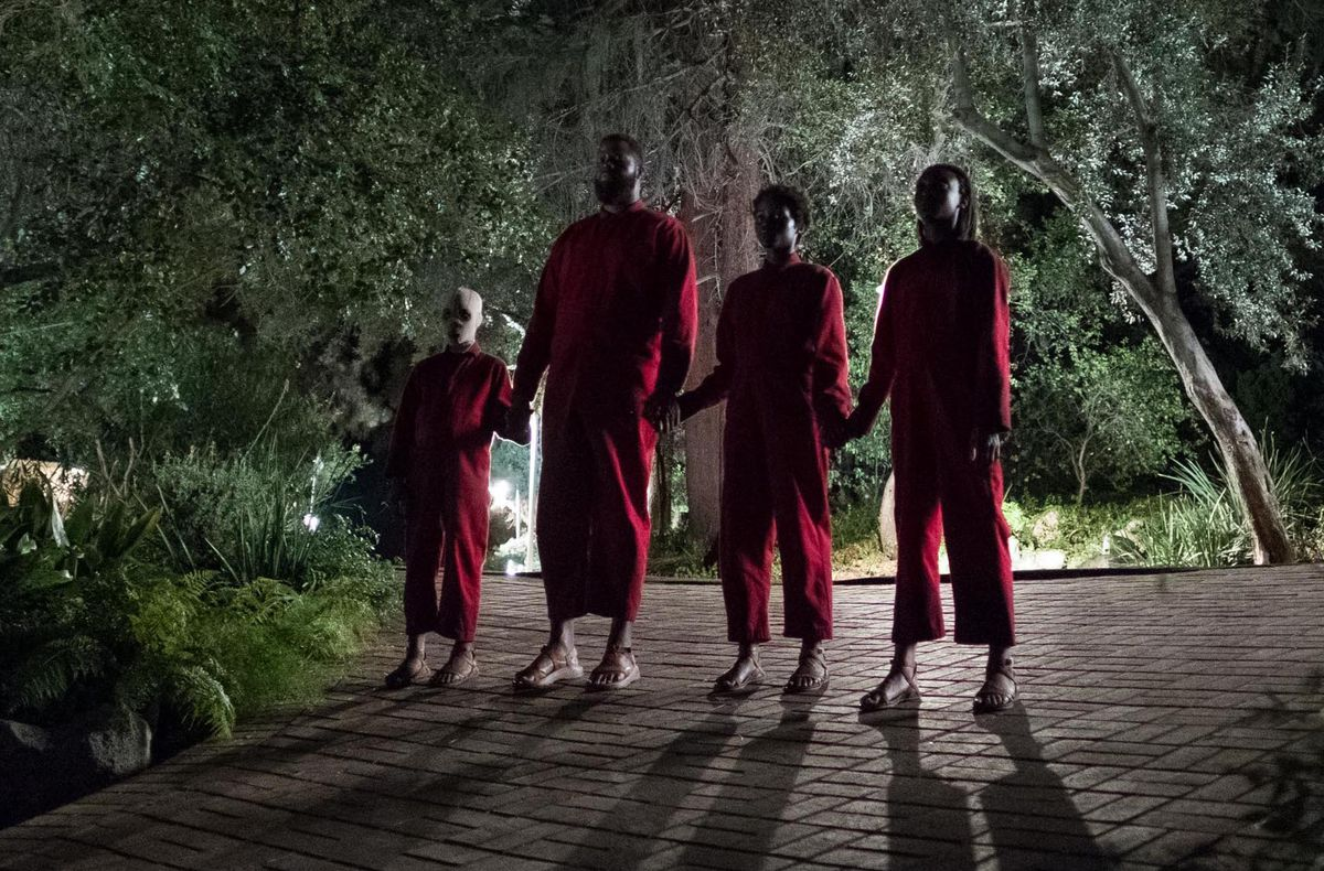 A black family of four stands in stark backlit silhouette on a patio, holding hands, with each member dressed in a blood-red jumpsuit.