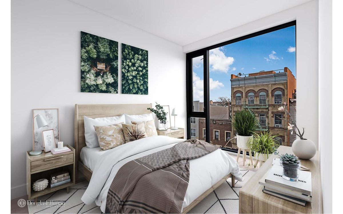 A bedroom with a medium-sized bed, a floor-to-ceiling window, and two planters.