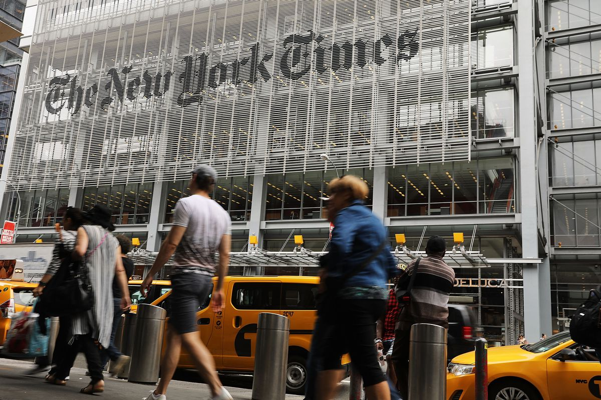 The New York Times building in New York, with pedestrians walking past in the foreground