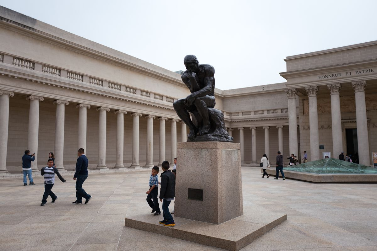 A white courtyard with a tremendous statue of a muscular man lost in ponderous thought, raised on a plinth.
