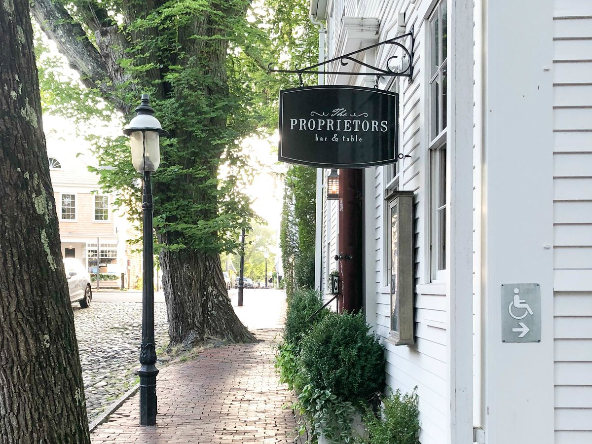 An elegant black sign for the Proprietors is attached to a white building on a brick, tree-lined sidewalk