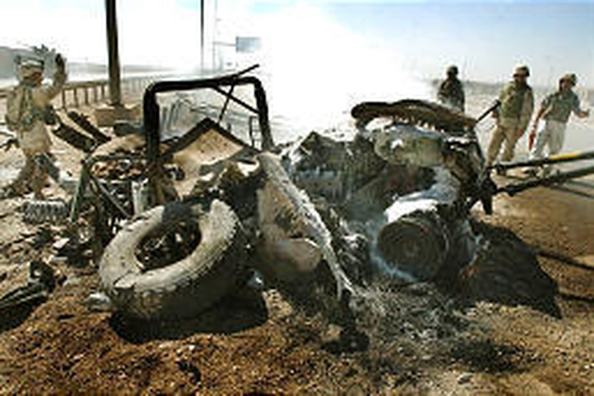 A team prepares to remove smoldering wreckage from humvee in Fallujah, Iraq, in which a soldier was killed.