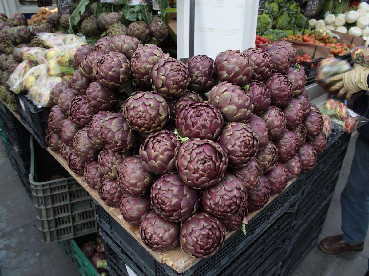 A stack of purple artichokes at a farmer's market