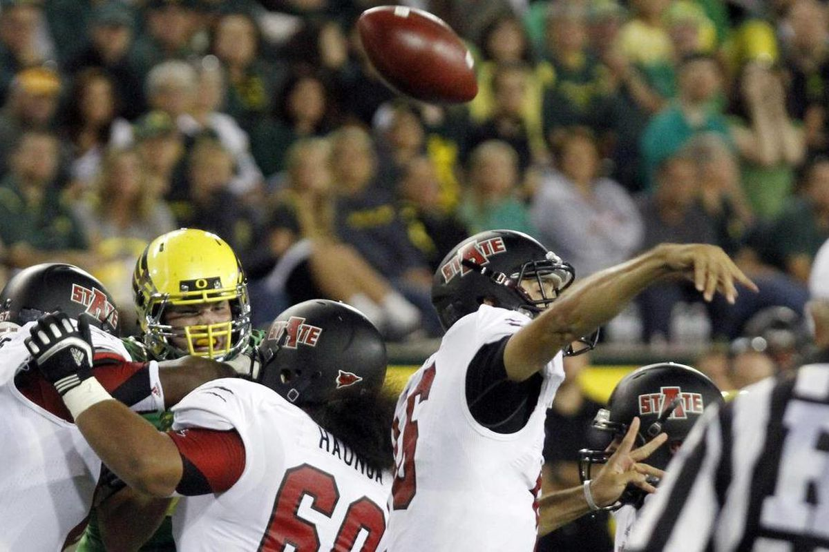 Arkansas State quarterback Ryan Aplin loses his grip on the ball while passing during the first half of their NCAA college football game against Oregon  in Eugene, Ore., Saturday, Sept. 1, 2012.  Aplin recovered his fumble on this play.