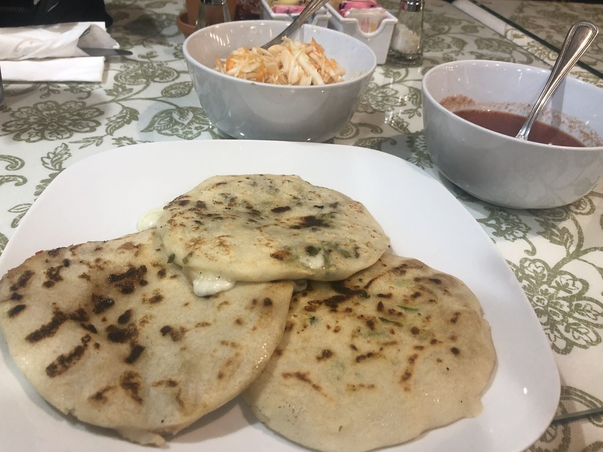 Three pupusas laid on a white plate with two white bowls filled with pickled cabbage and red tomato sauce sit on a green and white patterned table.