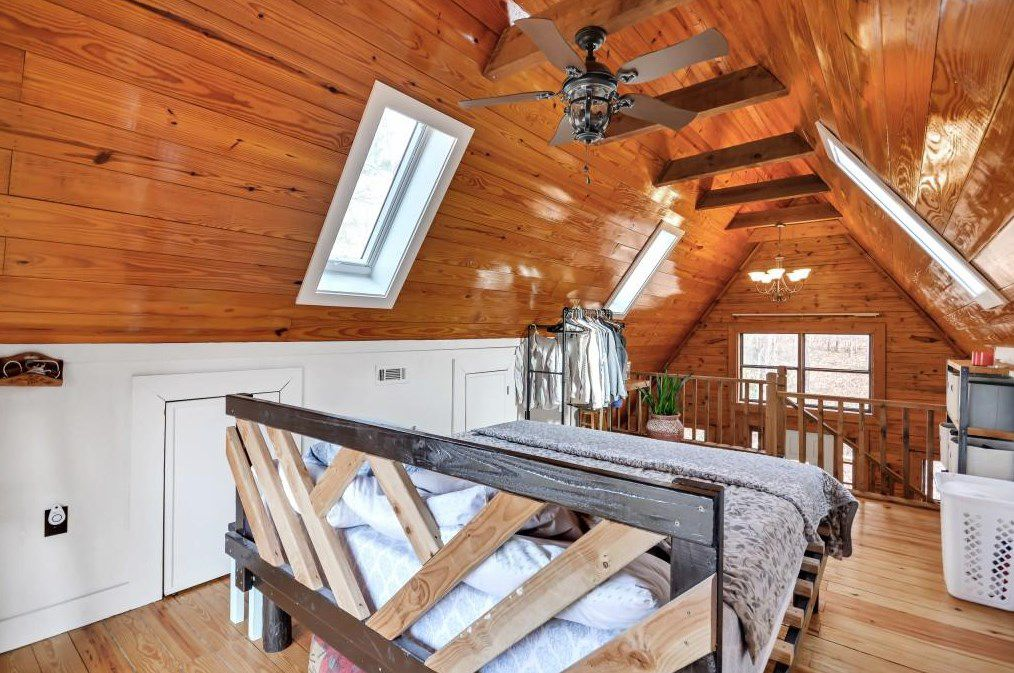 A bedroom in a cabin with skylights.