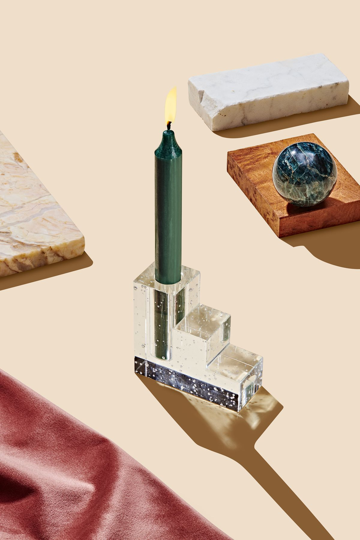 A glass candleholder holds a dark green lit candle. The candleholder has a terraced design with small bubbles. This is part of the Curbed Holiday Gift Guide 2019. The candleholder is surrounded by various design objects on a flat surface.
