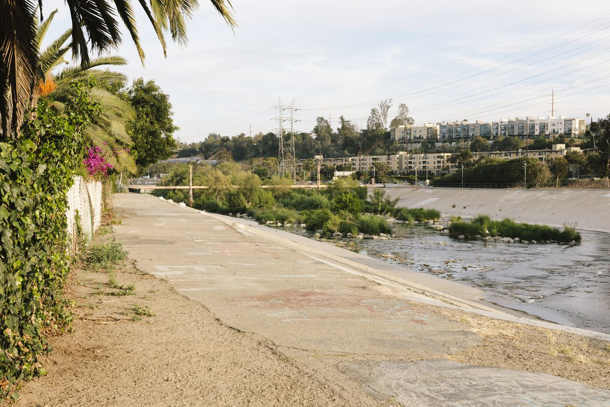 A sidewalk path along a riverbed. There are buildings in the distance.