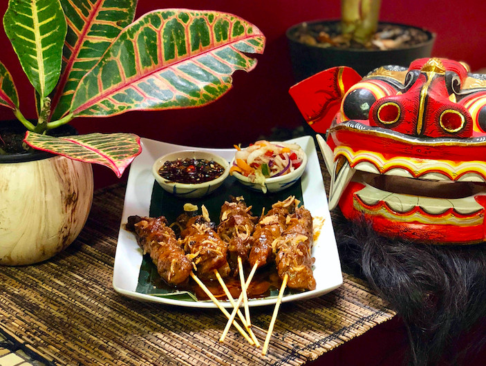 plate with sticks of grilled meat and bowls of sauce and vegetables next to plant and indonesian-style carved mask