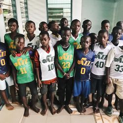 A group of Ghanaian children wear donated Jr. Jazz jerseys at a learning center in Abomosu. The center was built previously by World Joy of Bountiful, Utah. A group of Utah humanitarians from MRIoA and World Joy did fun crafts with the kids, making clothespin airplanes and popsicle stick picture frames.