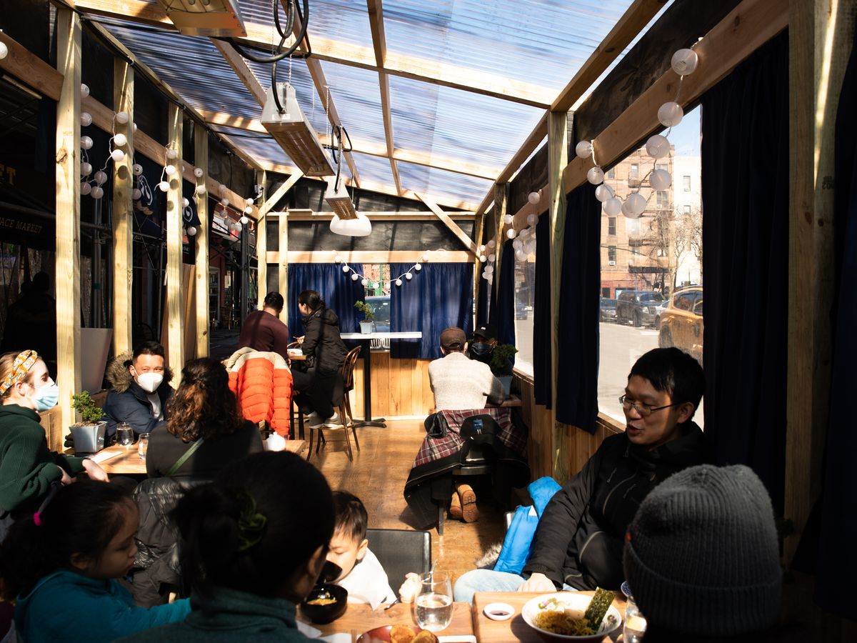 Diners eat outdoors in a covered plywood shed with electric heaters strung overhead