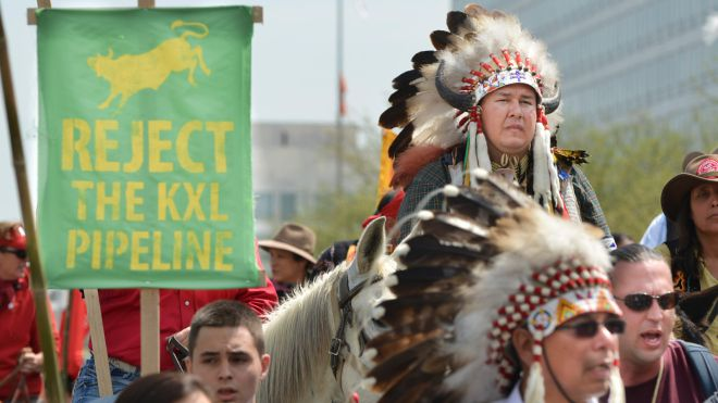 """Protesters with a sign: """"Reject the KXL pipeline"""""""