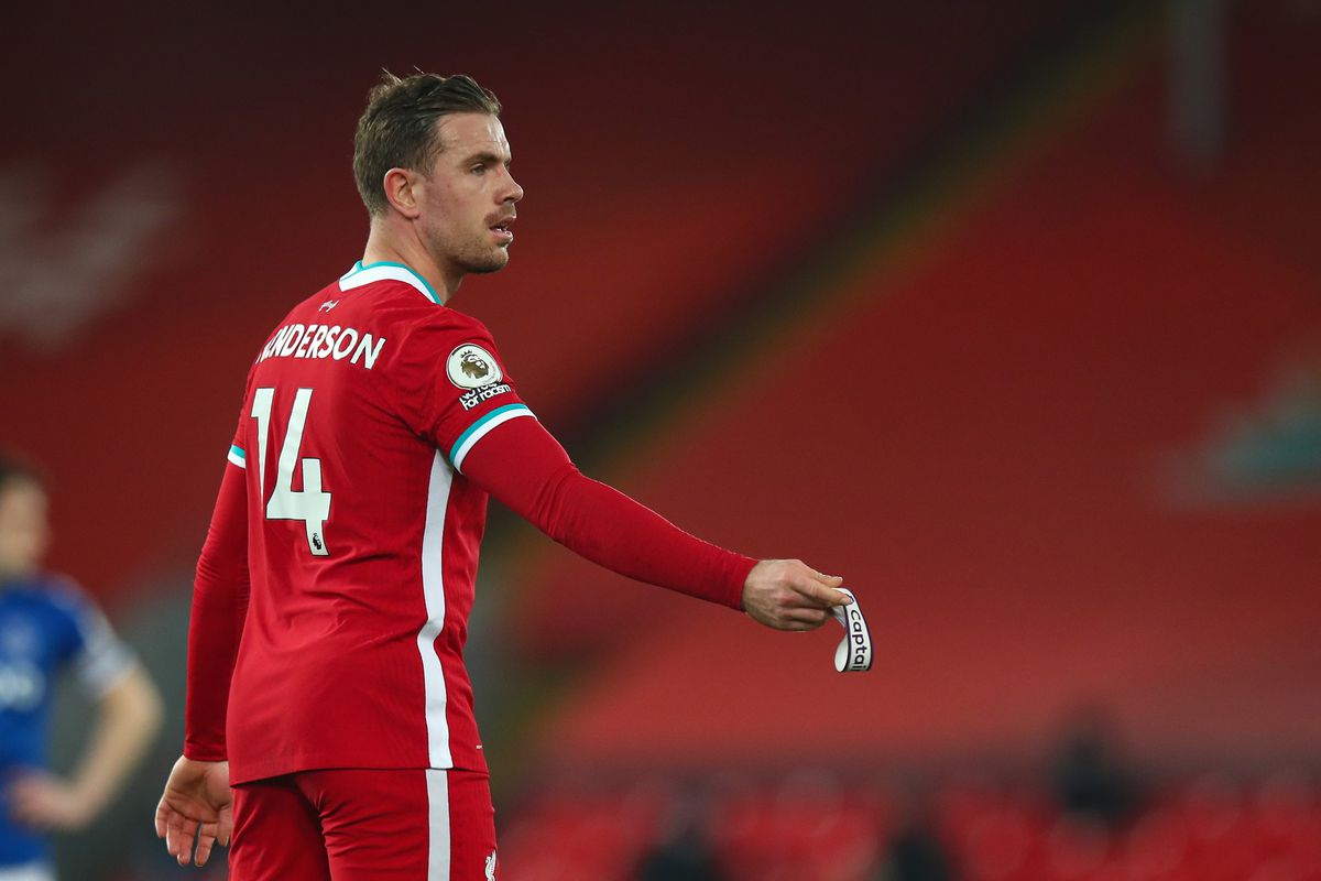 Jordan Henderson of Liverpool hands over the captains armband to Gini Wijnaldum after suffering a hamstring injury during the Premier League match between Liverpool and Everton at Anfield on February 20, 2021